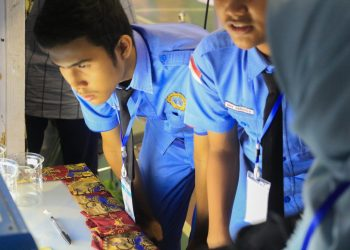 Pelajar SMA dengan  serius melihat mesin di stand Laboratorium Teknik Lingkungan