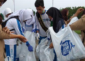 beberapa siswa sedang melakukan bersih-bersih di Pantai Purus, Padang,