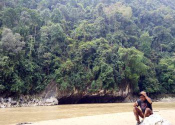Seorang wisatawan sedang duduk di sebuah batu di tepi sungai  pasir putih Nagari Silokek, Kabupaten Sijunjung, Provinsi Sumatera Barat.