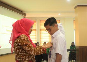 Dekan Fakultas Keperawatan Rizanda Machmud saat memasangkan Kartu Pengenal kepada salah seorang mahasiswa laki-laki Fakultas Keperawatan 2017 di Gedung Pascasarjana, Jumat (18/10/2019). (Foto : Rahmat Fiqri)