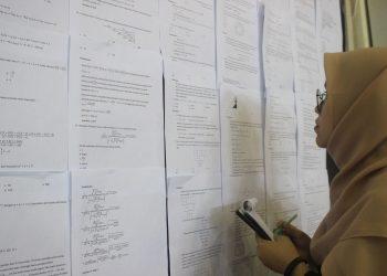 Seorang pengunjung memahami pembahasan soal yang terpampang dimading, Sabtu (8/2/2020). (Foto : Tiwi Veronika)