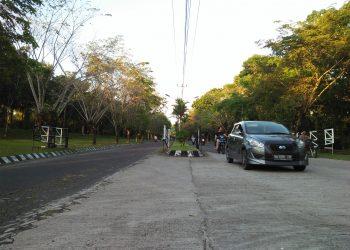Beberapa kendaraan melewati portal jalan utama Unand, Jumat (20/3/2020). (Genta Andalas/Icha Putri
