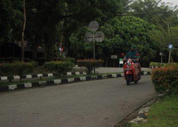 Pengendara sepeda motor melintas di depan Fakultas Kedokteran Unand, Minggu (26/04/2020) . (Genta Andalas/Rahmat Fiqri)