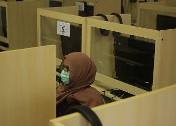 Peserta ujian melaksanakan ujian dengan mengenakan masker, sarung tangan, dan duduk berjarak dengan mengosongkan tempat di sebelhanya, Selasa (7/7/2020). (Rahmat Fiqri/Genta Andalas)
