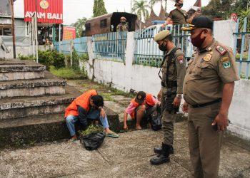 Terlihat dua orang pelanggar menggunakan rompi oren sedang membersihkan rerumputan di depan kantor KAN Pauh didampingi oleh personil Satpol PP, Rabu (14/10/2020). (Foto: Rahmat Fiqri).