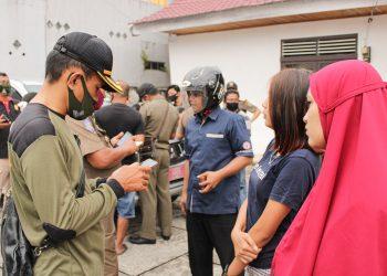 Petugas sedang menadata pelanggar dengan memasukan data secara online menggunakan ponsel di kawasan Pasar Baru, Rabu (14/10/2020). (Foto: Rahmat Fiqri)